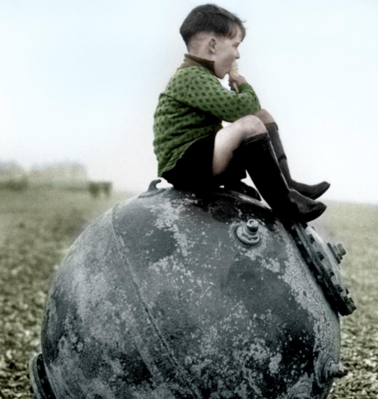 1945-Un-bambino-inglese-seduto-sopra-una-mina-marina-al-termine-della-guerra-color